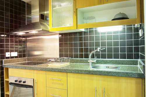 blue gray color of the granite countertop with the bold yellow cabinetry