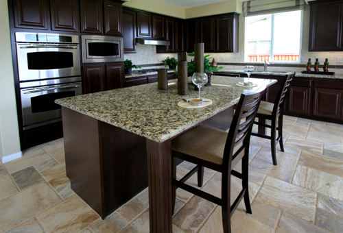 gorgeous slab of granite counter top extends well beyond the island cabinets
