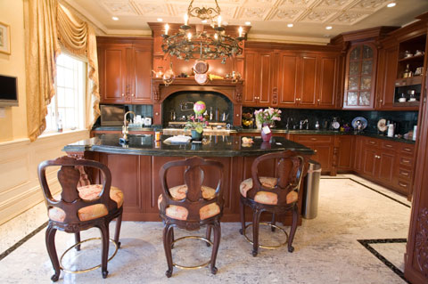 kitchen island features elegant cherry wood panelled cabinets